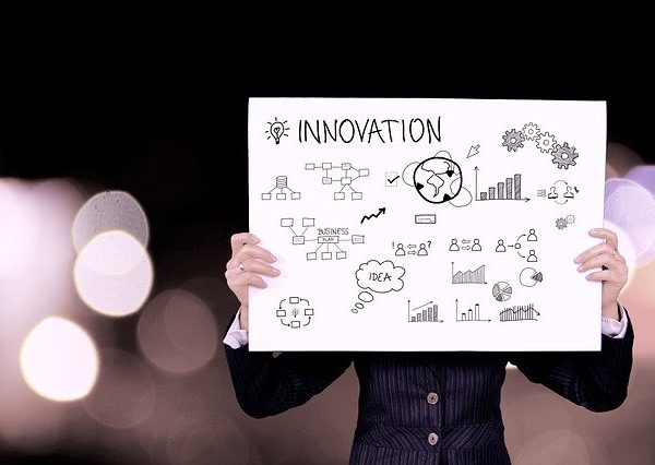 man-holding-board-of-innovation-words